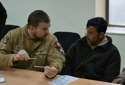 WO Milan R. explains procedures before testing of helicopter weapons to his Afghan colleague