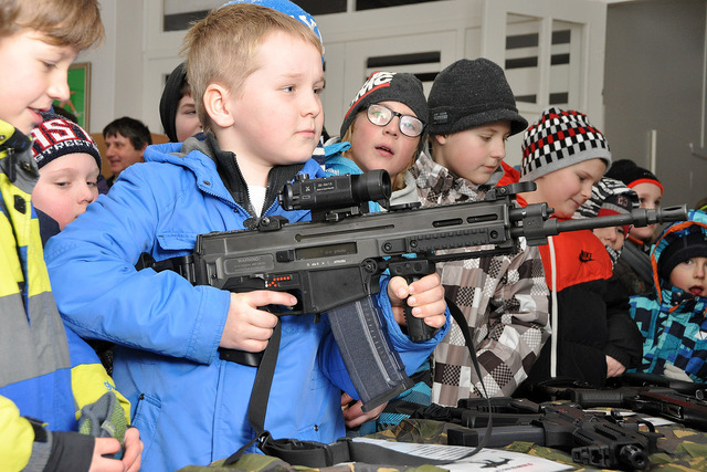 Boys enthusiastically examining weapons