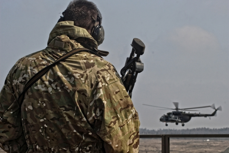 A sniper observing a helicopter hovering scene